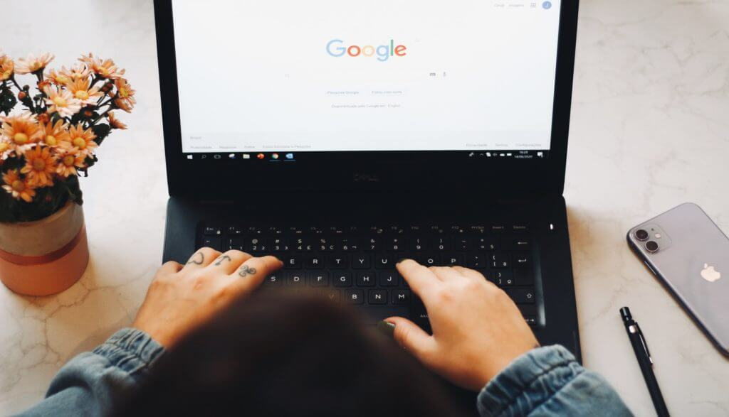 Hands typing on laptop. Computer displays Google home page.